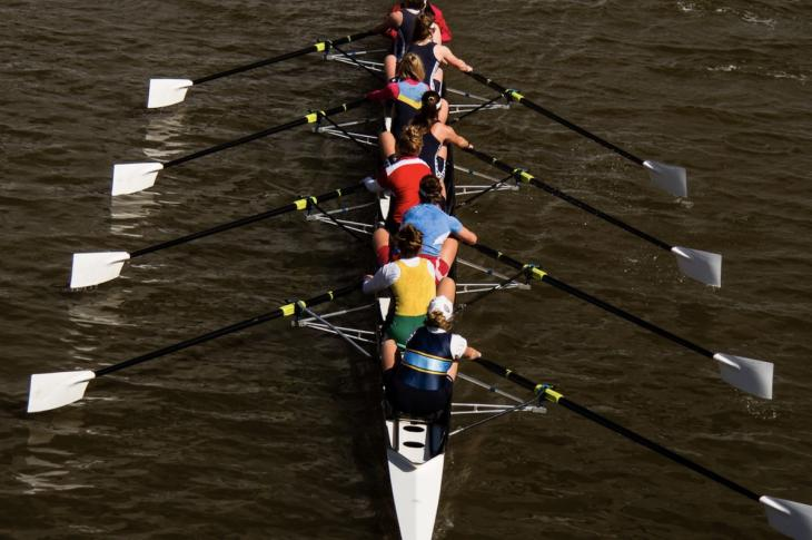 boat rowers all pull together to row in unison for a team effort