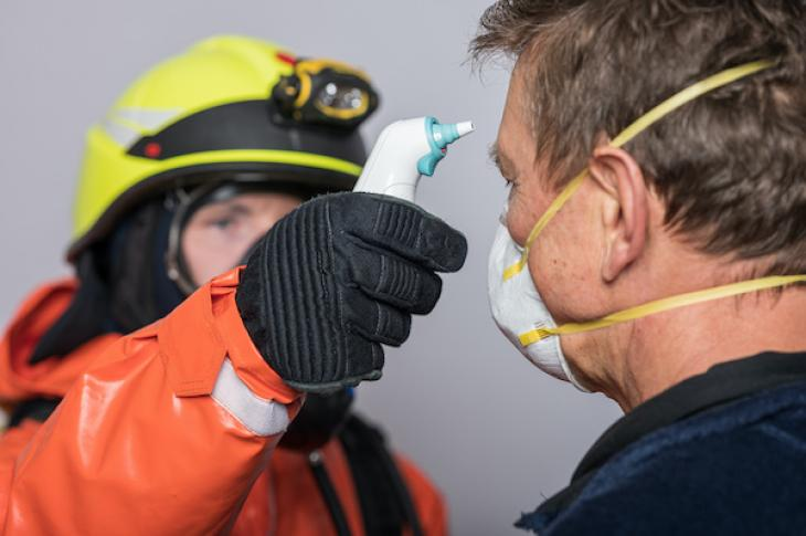man in protective gloves measures temperature of man wearing face mask