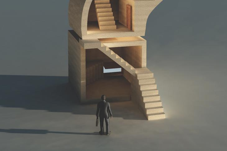 businessman looking at stairs to where as he considers the future of his business