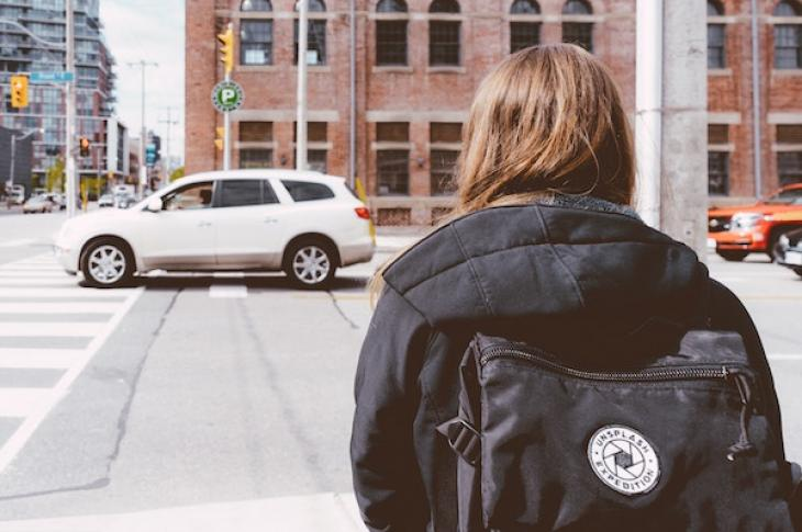 Girl_with_backpack_looking_at_car