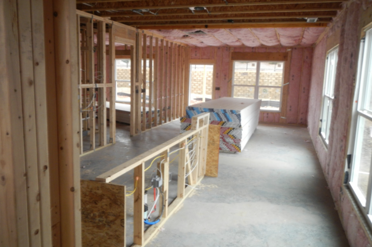 framed home interior with insulation installed and drywall neatly stacked on a clean jobsite