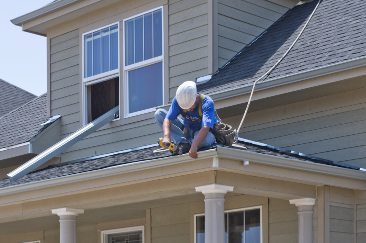 construction worker on roof installing gutter in Denver on net zero energy ready new home