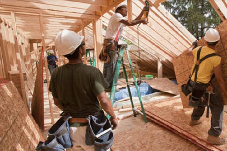 Construction workers framing house under construction