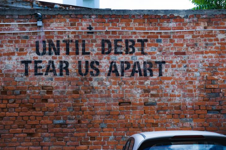 Mural 'until debt tear us apart' on brick wall
