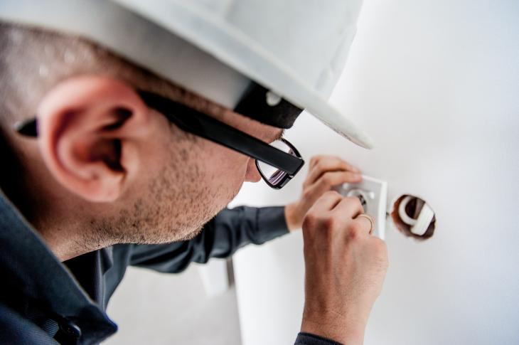 construction worker wearing hard hat installing electrical outlet in wall