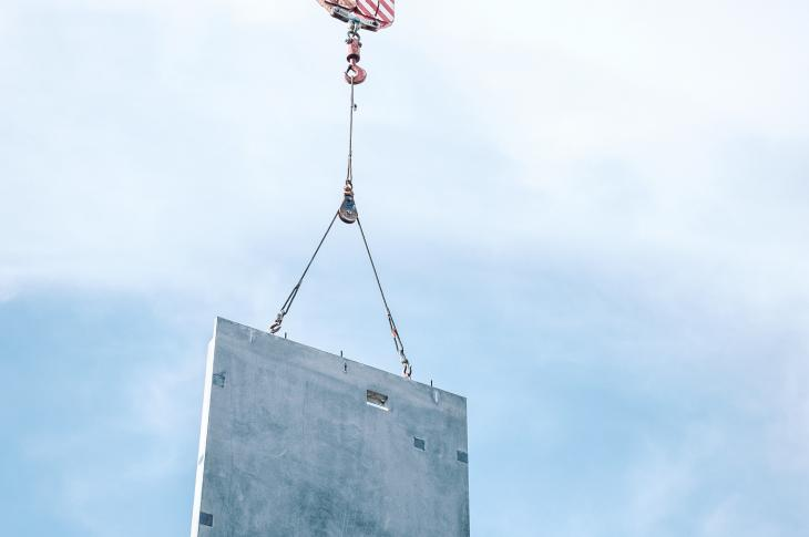 Prefab wall panel being lowered into place by a crane