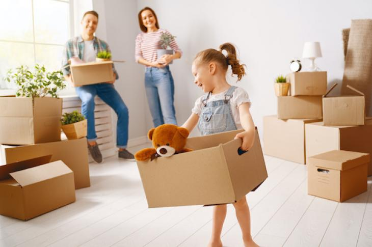 Family with young child moving cardboard boxes into new home