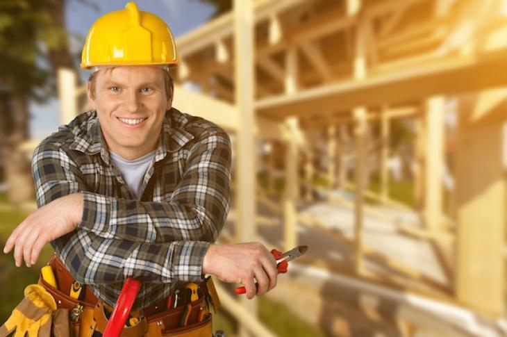 home builder leaning on tools in front of framing