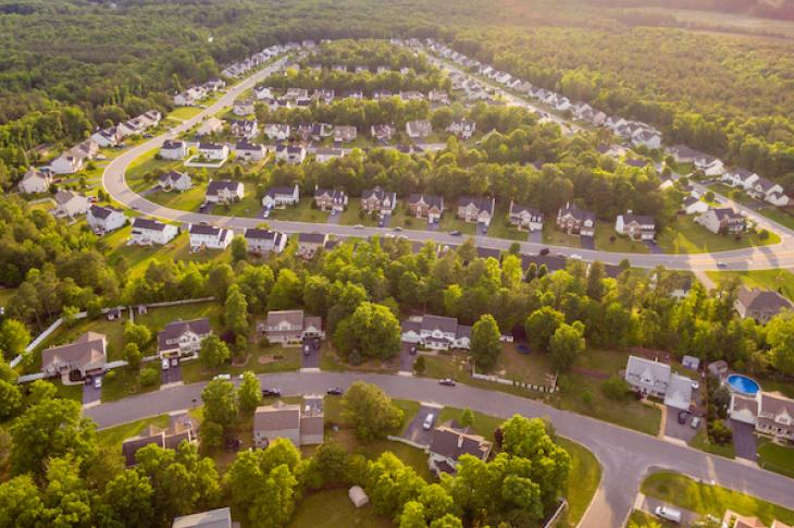 aerial view of housing subdivision surrounded by trees and green space