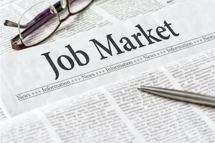 Jobs market report with pen and reading glasses