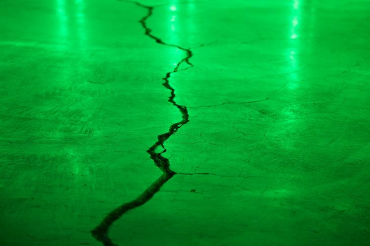 Crack in concrete with green light
