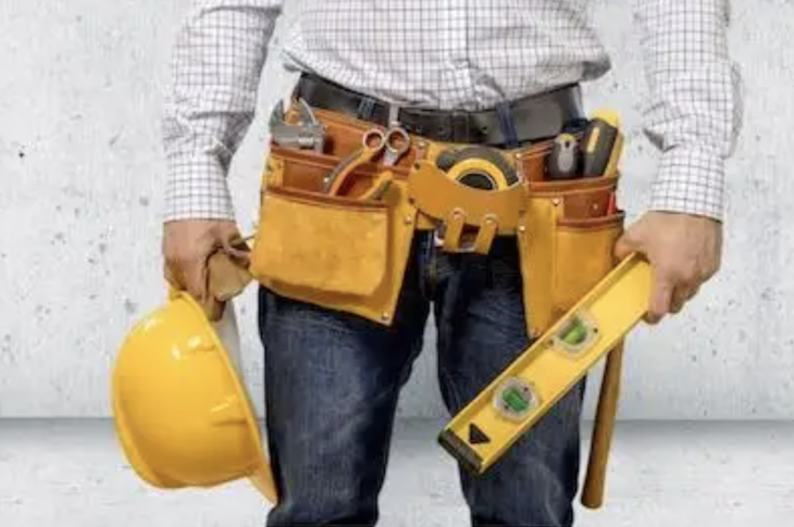 man wearing toolbelt and holding a hard hat and level