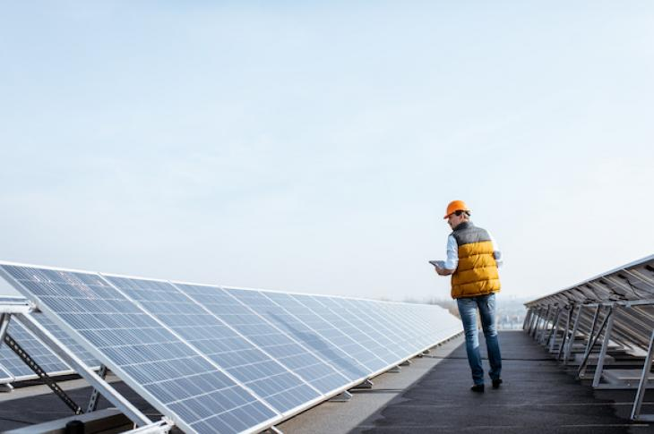 Man Walking looking at solar panels