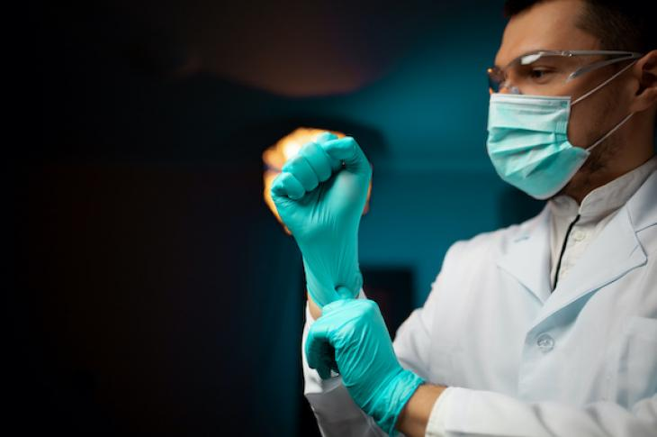 healthcare worker wearing protective face mask putting on latex gloves