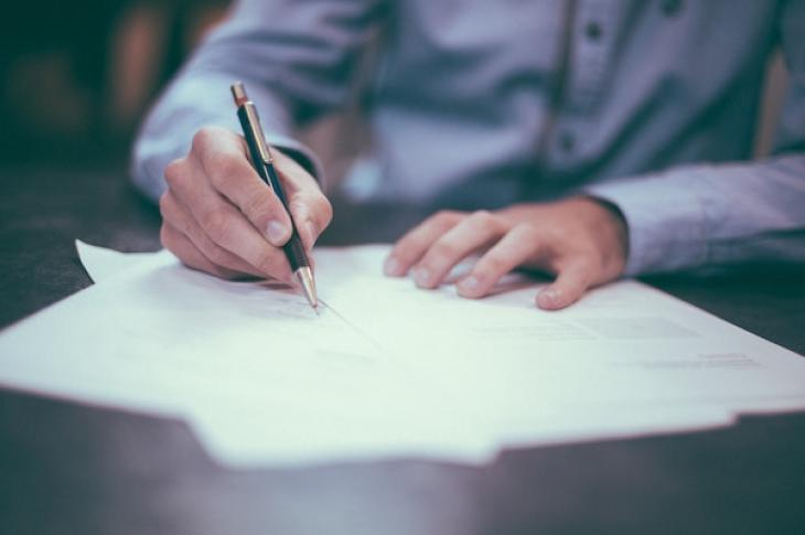 Hands_signing_contract_on_desk