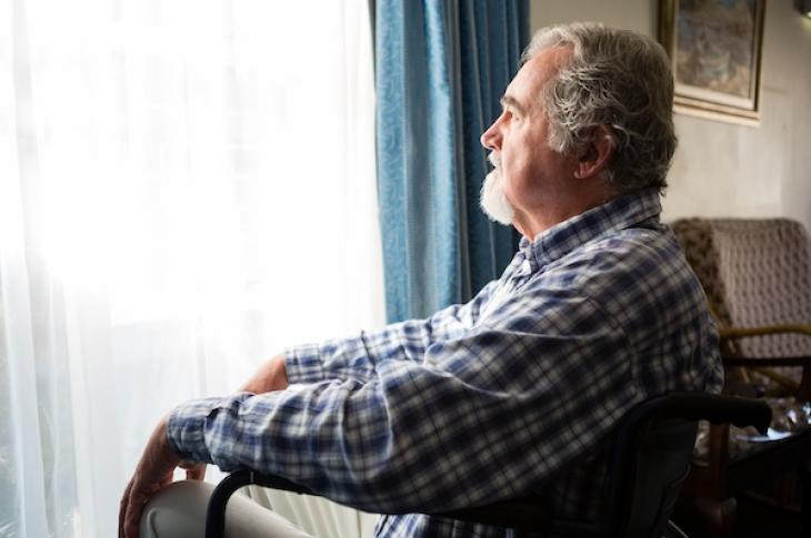 Retired man looking at window