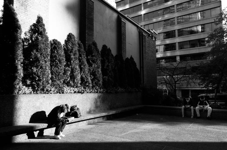 Three people on benches in city in b/w photo