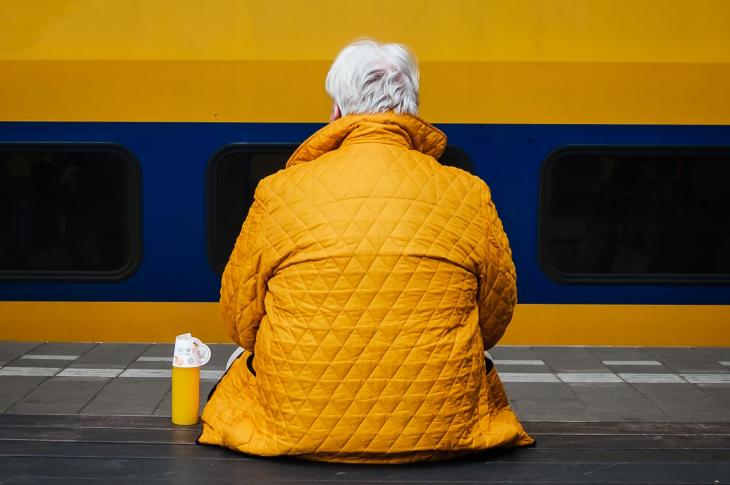 Senior man sitting at train station