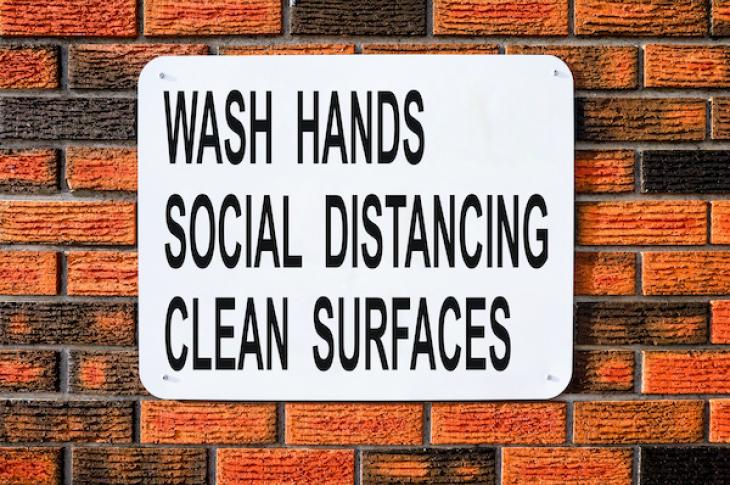 black and white sign on brick wall says wash hands, clean surfaces, and practice social distancing