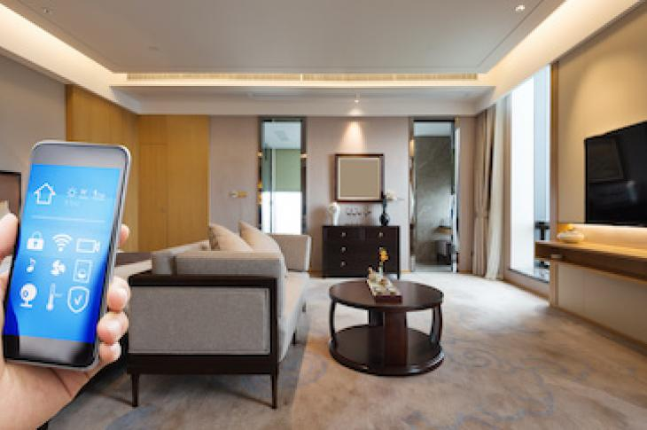 hand holding smartphone in a smart home