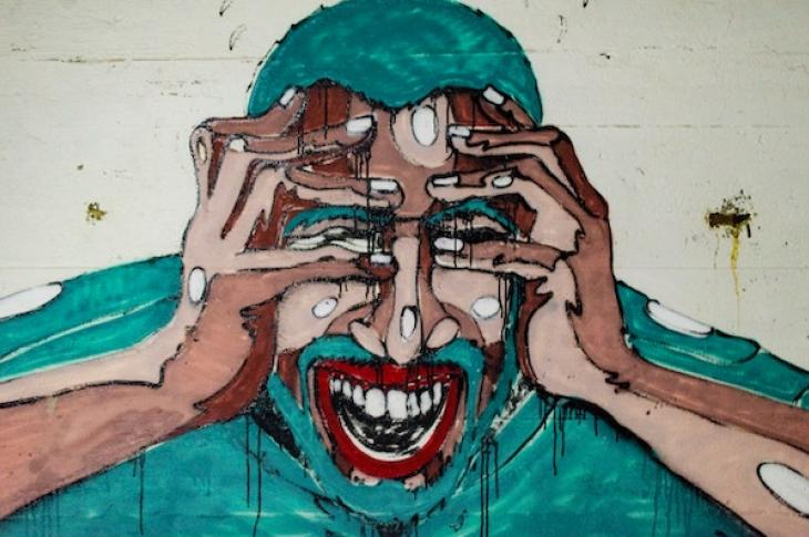 city mural of stressed man holding his head