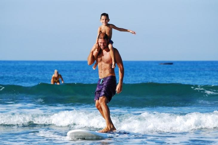 Boy_on_shoulder_of_man_surfing