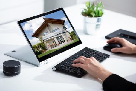 Person viewing an online listing of a home for sale