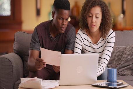 Black couple looking at homes online