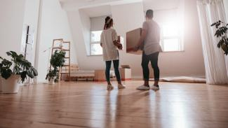 Couple in new house holding moving boxes