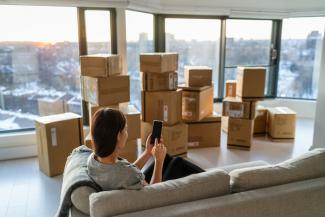 Woman sitting in city skyrise with moving boxes