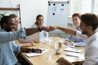 Company culture image of co-workers fist bumping at conference table