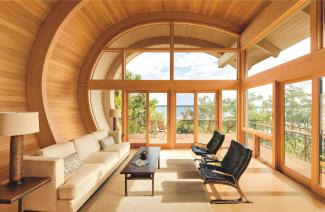 Wood windows and doors from Marvin installed in a home with a unique curved roof design