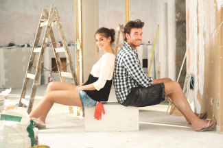 man and woman sit back to back on box with ladder in middle of home renovation project