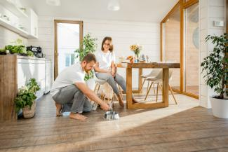 Couple feeding dog in bright room