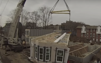 Crane lifting prefabricated apartment building modules into place