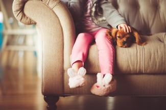 child wearing bunny slippers sitting on sofa with puppy stirs emotions