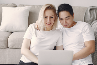 man and woman doing home buying research together on laptop