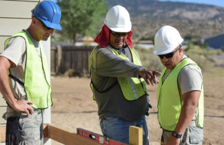 foreman pointing out a mistake on a construction site to two other crew members