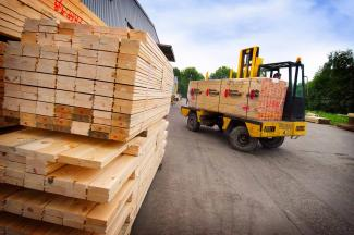 Group purchasing pros and cons in the lumberyard with stacks of lumber for construction
