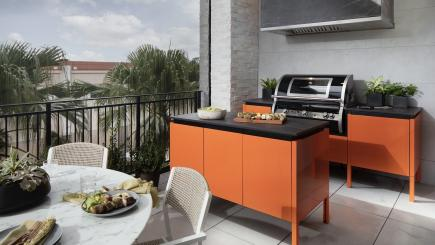 Brown Jordan outdoor kitchen cabinets in bright orange for The New American Home 2021