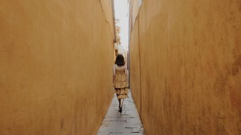 Woman walking in narrow space between two tall walls