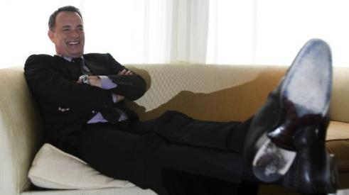 Actor Tom Hanks sitting on a sofa with his feet up, relaxing