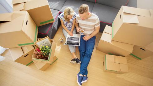 Young couple sitting on floor around moving boxes