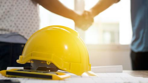 Two people shaking hands with hard hat in foreground