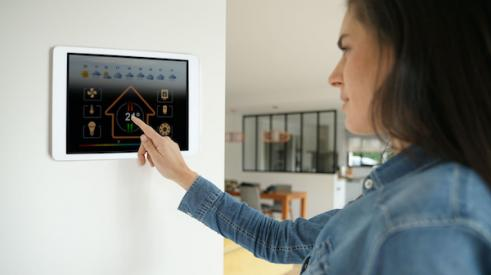 Woman using smart home touch screen on wall