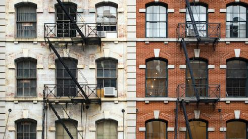 Exterior of two brick New York City apartment buildings with fire escapes