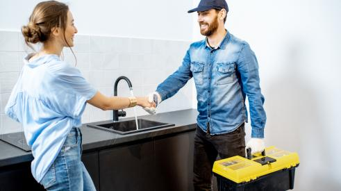 Woman shaking plumber's hand