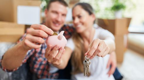 Homeowners smiling and putting coin into piggy bank