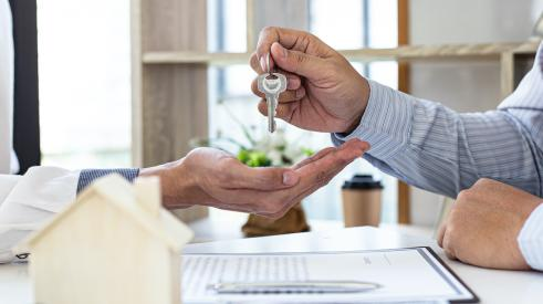 Person handing over home keys