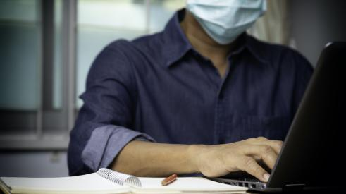 Man working at laptop with mask